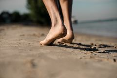 Person walking on sand beach leaving footprints on the sand. Close up photo of person walking on sand beach leaving footprints on sunny summer day Royalty Free Stock Image