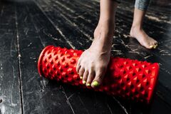 Close-up photo of pilates trainer girl feet massaging foot with sports foam red cylinder to work out fascia