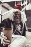 Close up photo of plastic cup which holding by old man. Means of earnings. Close up photo of plastic disposable cup which holding by old man with grey long hair stock photography