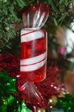 A close up photo of a plastic red and white candy ornament with carolers at the bottom on a Christmas tree Royalty Free Stock Photo