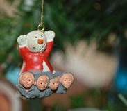 A close up photo of a plastic snowman ornament with carolers at the bottom on a Christmas tree Stock Images