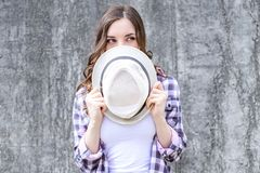 Close up photo portrait of pretty beautiful cunning sly shy lady hiding face behind headwear cap hat looking aside grey b royalty free stock image