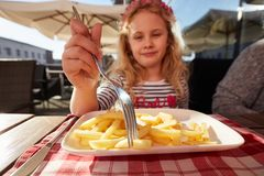 Close up photo preschool girl eats french fries potatoes sitting in cafe outdoors. Close up photo preschool girl eats french fries potatoes sitting in cafe stock photography