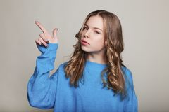 Close up photo of cute attractive girl teenage showing to empty space attention on novelty wearing bluer pullover grey background. Close up photo of pretty cheer royalty free stock photos