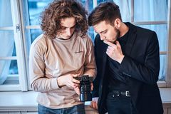 Professional curly photographer man showing photos on digital camera to suit dressed custumer. Close up photo of professional curly photographer men showing stock images