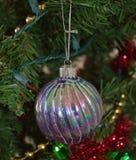 A close up photo of a rainbow glass Christmas bulb ornament on a Christmas tree. A close up photo of a silver and rainbow glass Christmas bulb ornament on a Stock Photos