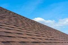 Asphalt tile roof on new home under construction. Close up photo of roof shingles installed on top of the new modern house under construction against beautiful stock images