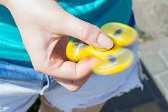 Close up photo of rotating yellow fidget spinner in girl`s hands cropped closeup view photo of teen teenager playing with spinner royalty free stock photos