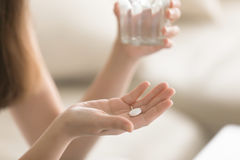 Close up photo of round white pill in female hand. Close up photo of one round white pill in young female hand. Woman takes medicines with glass of water. Daily Royalty Free Stock Image
