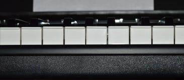 A close-up photo satin black and white portable digital piano. Keys Royalty Free Stock Photography