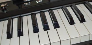 A close-up photo satin black and white portable digital piano. Keys Stock Photography