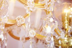 Close-up photo of the scenery on the old chandelier. Glass figures shine and reflect light with their faces.  stock photo