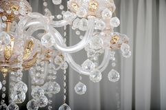 Close-up photo of the scenery on the old chandelier. Glass figures shine and reflect light with their faces.  royalty free stock photography