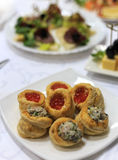Close up photo with selective focus of red caviar profitroles served on white table next to salad profitrole Stock Photo