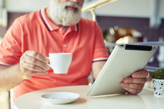 Close-up photo of senior bearded man with cup of coffee Royalty Free Stock Images