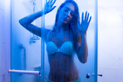 Close-up photo of sexy young woman taking a shower wearing bikini in bathroom Royalty Free Stock Photo