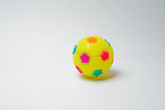 Close-up photo of a small yellow ball on a white background. Royalty Free Stock Image