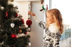 Close-up photo of smiling little blonde girl in knitted sweater. Hangs red bauble on Christmas tree Royalty Free Stock Photos