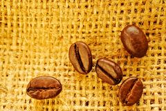 Coffee beans on burlap background. Close up photo of some coffee beans on burlap background Royalty Free Stock Photo