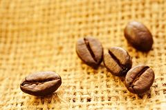 Coffee beans on burlap background. Close up photo of some coffee beans on burlap background Royalty Free Stock Image