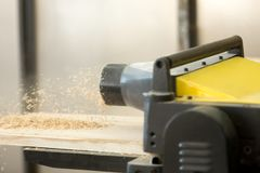 Thickness planer machine in woodworking workshop. Close up photo of stationary powerful woodworking machine tool throwing out sawdust while reducing thickness of Royalty Free Stock Photography