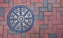 A rustic manhole cover on a brick sidewalk. royalty free stock photography