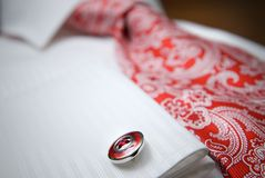 Close-up photo of stud on white shirt with red tie. Close-up photo of stud on white shirt with nice red tie Stock Image