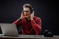 Close up photo of student listening to music while working in the laptop. Close up photo of student listening to the music while working in the laptop Royalty Free Stock Photography