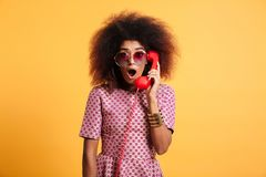 Close-up photo of surprised retro woman with afro hairstyle hold. Ing retro phone, looking at camera, isolated over yellow background Stock Image