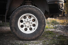 Close-up photo of SUV car wheel. On dirty rural road with grass, front view Royalty Free Stock Images