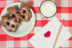 Close up photo of tasty biscuits glass of milk and envelope with. Love letter inside on checkered background Stock Photography