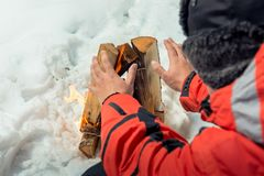 Close-up photo - tourist warms his hands near the fire. In the winter forest Stock Photos