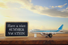 Close up photo of toy airplane next to blackboard with text: HAVE A NICE SUMMER VACATION, against sky with clouds Royalty Free Stock Images