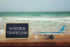 Close up photo of toy airplane next to blackboard with text: SUMMER TRAVELING, against sea waves. vintage filtered image. Selective focus stock images