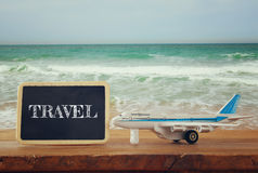 Close up photo of toy airplane next to blackboard with text: TRAVEL, against sea waves. vintage filtered image, selective focus.  royalty free stock photography
