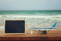 Close up photo of toy airplane next to blank blackboard against sea waves. vintage filtered image, selective focus.  royalty free stock photos