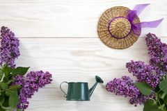 Close up photo with toy watering can, Little straw hat and lilac on white wooden background. Spring background, top view, close up. Close up photo with toy royalty free stock images