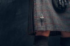 Traditional Scottish costume. Kilt and sporran. Close-up photo of a traditional Scottish costume against a dark textured wall. Kilt and sporran royalty free stock photo