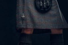 Traditional Scottish costume. Kilt and sporran. Close-up photo of a traditional Scottish costume against a dark textured wall. Kilt and sporran stock photography