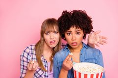 Close up photo two diversity she her ladies different race skin open mouth oh no awful film food pop corn wtf face wear. Casual jeans denim checkered shirt stock image