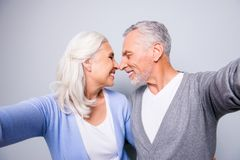 Close up photo of two happy cheerful lovely tender gentle sweet. Senior couple, they are taking a self portrait, hugging each other and touching noses, isolated Royalty Free Stock Photos