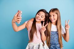 Close up photo two little she her blond brunette girls long pretty hair telephone make take selfies for mom mommy show v royalty free stock photo