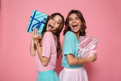 Close-up photo of two overjoyed female friends in colorful tshir. Ts holding gift boxes, looking at camera, isolated on pink background Royalty Free Stock Image