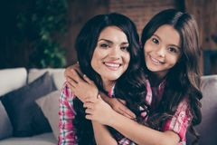 Close up photo two people cuddle mum little daughter satisfied adorable piggy back carry hold wear pink plaid shirts. Flat apartment room comfortable cozy couch royalty free stock photos