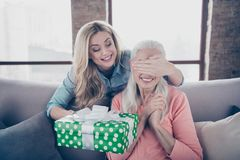 Close up photo two people she her ladies mom child grandmother not wait grandchildren holiday not see giftbox hide eyes. Ask guess who casual domestic clothes royalty free stock photo
