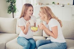 Close up photo two people mom and teenager daughter communicating buddies hold hot beverage sweets hands arms tell speak. Best friends wear white t-shirts jeans stock image