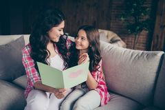 Close up photo two people mum little daughter giving postcard with mommy poem unexpected sweet cute reading delighted. Wear pink plaid shirts flat apartment royalty free stock photography
