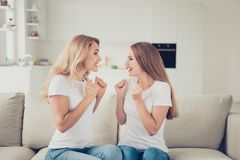 Close up photo of two people mum mommy and teen daughter holding fists near chest satisfied nice news win money free. Shopping wear white t-shirts denim jeans royalty free stock photo