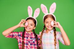 Close up photo of two pretty little age girls holiday concept with bunny ears on head hiding one eye behind easter. Colored eggs wearing casual checkered plaid stock images