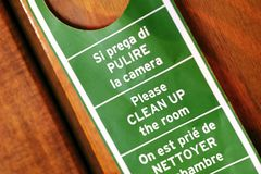 Clean up the room. Close up photo of a typical hotel door sign: green sign at red wooden background. If some guest needs a cleaning service in the room - he puts Royalty Free Stock Photo